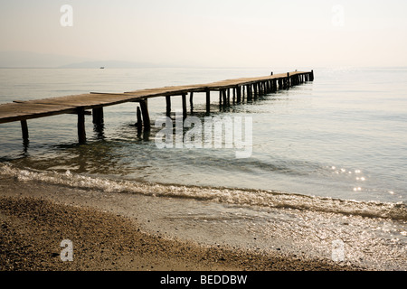 wooden jetty at the beach of Ipsos, Corfu, Greece, in the morning - Stock Photo