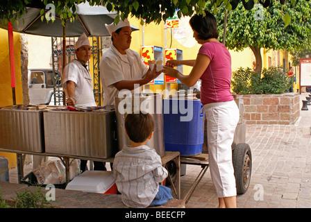 Woman buying ice cream from a street vendor in San Miguel de Allende, Guanajuato, Mexico - Stock Photo