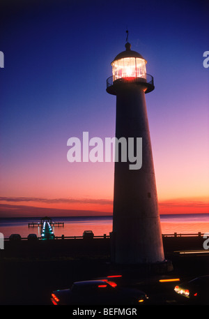The Old Biloxi Lighthouse on Gulf of Mexico in Mississippi with passing traffic at dusk - Stock Photo