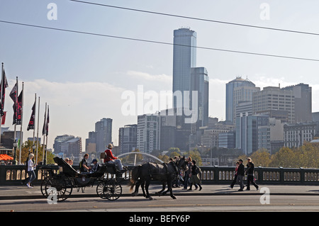 Horse drawn Landau carriage crossing Princes Bridge over Yarra River with high rise skyscrapers Melbourne Australia - Stock Photo