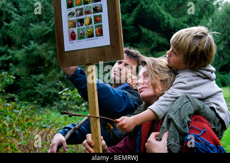Mother carrying child on shoulders learning about nature by reading wildlife information board along educational - Stock Photo