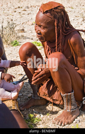 Old Himba woman in a village near Epupa Falls, Namibia, Africa. - Stock Photo
