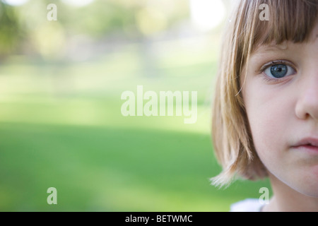 seven year old girl looking at camera with serious expression, green background, outdoors, closeup of face - Stock Photo