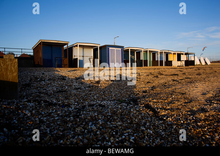 Beach huts on the stoney beach at Shoeburyness in the late autumn sunshine,  near Southend on Sea, Essex, UK - Stock Photo