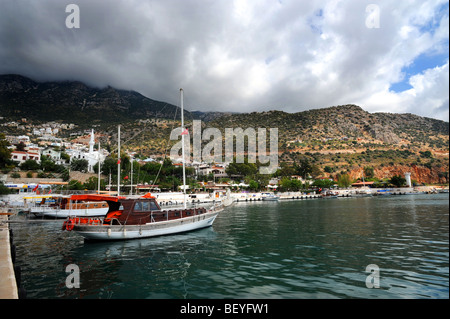 Small boats moored in the bay of kalkan under a cloudy sky - Stock Photo