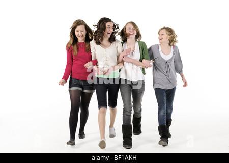 4 teenage girls linking arms walking towards camera smiling - Stock Photo