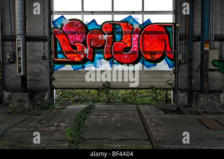 Abandoned industrial hall, sliding gate with graffiti, former Ausbesserungswerk repair shop of German Railways, - Stock Photo