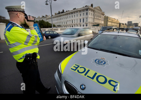 A police officer using a handheld laser camera on a city road to catch speeding motorists - Stock Photo