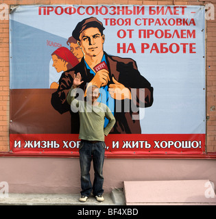 Man standing in front of traditional soviet propaganda poster, portrait, Ekaterinburg, Urals, Russia - Stock Photo