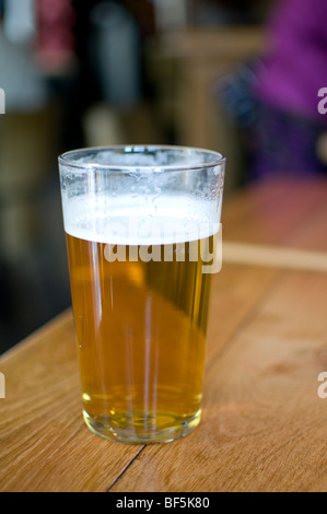 A pint of real pale ale on a table in a typical english pub - Stock Photo