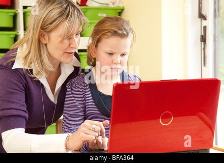 teacher / assistant  helping young girl to use a computer - Stock Photo