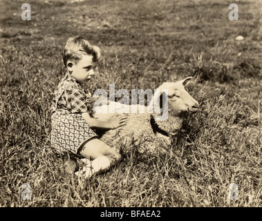 Boy Holding Lamb in Pasture - Stock Photo