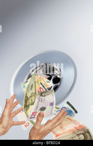 money going down the plughole into sink drain conceptual image - Stock Photo