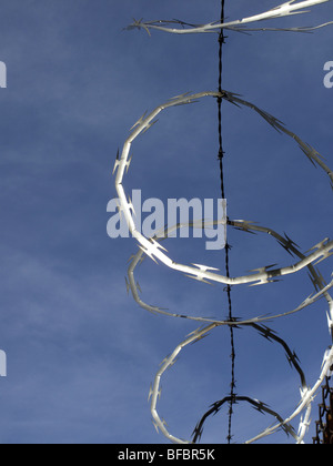 Rolled razor wire on top of a fence in New York City reflects the sunlight against a deep blue sky - Stock Photo