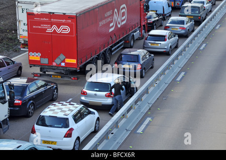Motorist out of their vehicle in gridlocked traffic on M25 motorway roadworks section after closing due to accident - Stock Photo