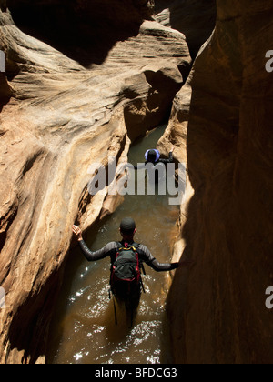 Two people wade through water while hiking down a slot canyon in Utah. - Stock Photo
