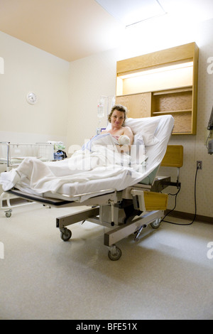 36 year old woman lying in hospital bed with newborn in her arms, Chateauguay, Quebec, Canada - Stock Photo