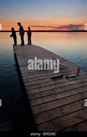 A father with his two sons fishing at the end of a wharf on Lake Audy at sunset, Riding Mountain National Park, - Stock Photo