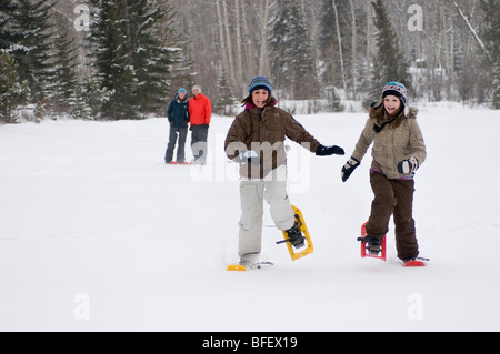 Two young girls race across Pyramid lake in snowshoes as parents look on, in Jasper National Park, near Jasper, - Stock Photo