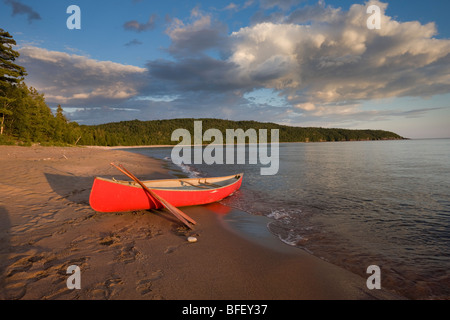 Red canoe on sandy beach of Gargantua Bay in Gargantua Harbour on Lake Superior in Lake Superior Provincial Park - Stock Photo