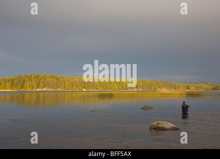 Fisherman fly-fishing in a small river, Finland - Stock Photo