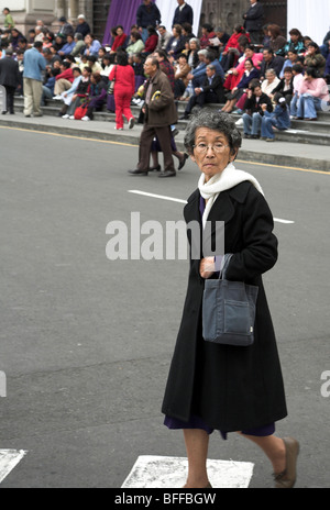 Lima, Peru,  Plaza de Armas or Plaza Mayor:  Lord of Miracles 2006, a woman crossing the street - Stock Photo