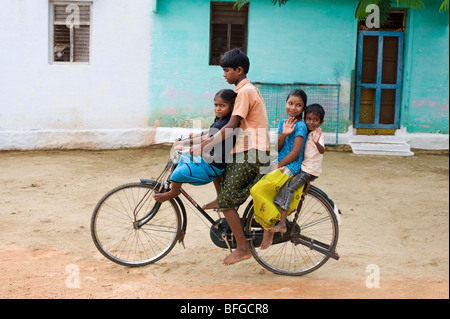 Indian teenager and children riding a bicycle in a rural Indian village. Andhra Pradesh, India - Stock Photo