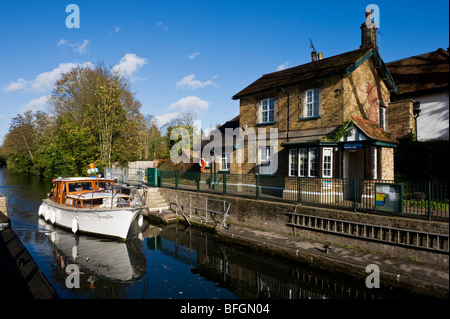 A boat passing a traditional riverside lock keeper's cottage at Boulters Lock on the River Thames near Maidenhead - Stock Photo