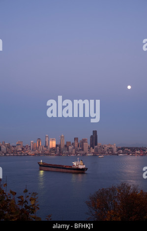 Seattle skyline from West Seattle with tankers in Elliott Bay at sunset with moonrise and city lights Washington - Stock Photo