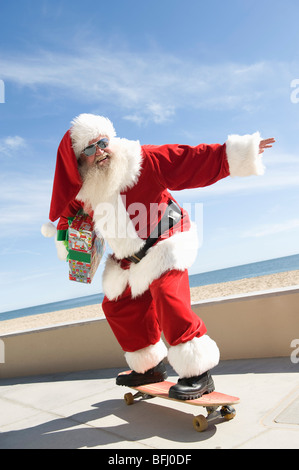 Father Christmas skateboards - Stock Photo