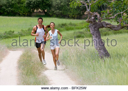 Couple running on path through rural field - Stock Photo