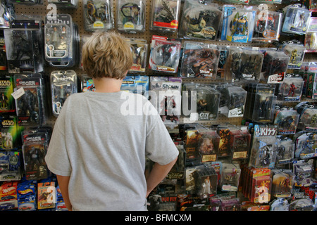 ten year old boy buying action figures in a toy store - Stock Photo