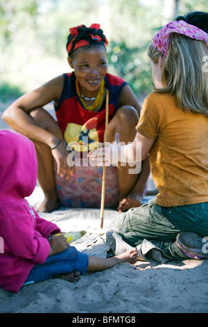 Nhoqma village, Bushmanland, Namibia. Ecotourism project, a young girl learns how to make ostrich-shell jewellery - Stock Photo
