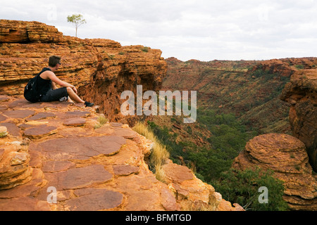 Australia, Northern Territory, Watarrka (Kings Canyon) National Park.  A hiker looks out over Kings Canyon. (MR) - Stock Photo