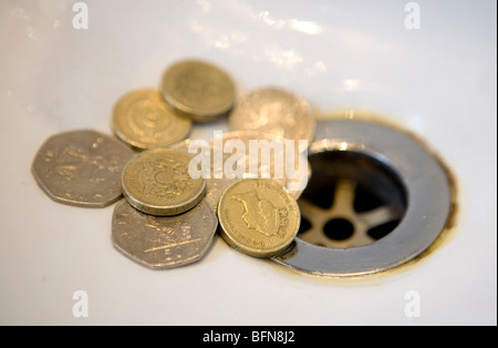 English money going down the drain - Stock Photo