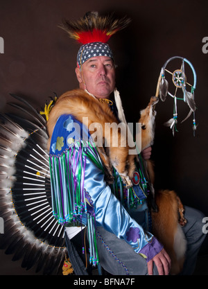 Native American Indian Male in full regalia with eagle feather bustle and draped in fox pelts holding dream catcher - Stock Photo