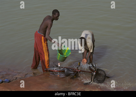 Bozo fishermen take a break from their nets to clean a bicycle in the Niger River - Stock Photo