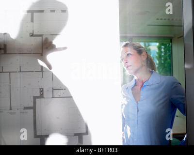 Man and woman behind blue prints - Stock Photo