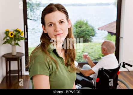 woman caring for man in wheelchair - Stock Photo