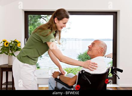 woman touching man in wheelchair - Stock Photo