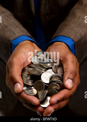 Business man with handful of coins - Stock Photo