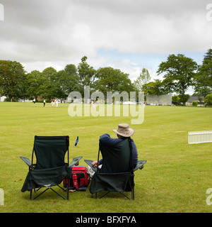 man sitting in folding chairs watching cricket match - Stock Photo