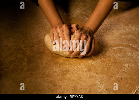 Person kneading bread dough on a marble surface, close up looks very old world - Stock Photo