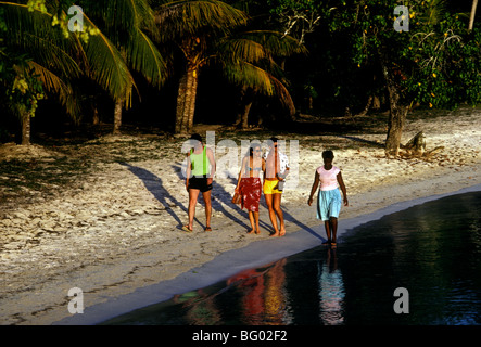 Jamaican woman, tourists, walking along beach, Negril, Jamaica - Stock Photo