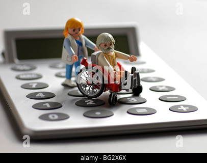 Playmobil toys on a calculater . - Stock Photo