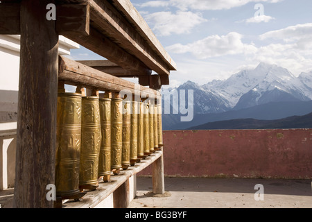 Prayer wheels with Meili Snow Mountain peak in the background, near Tibetan border, Shangri-La region, Yunnan Province, - Stock Photo