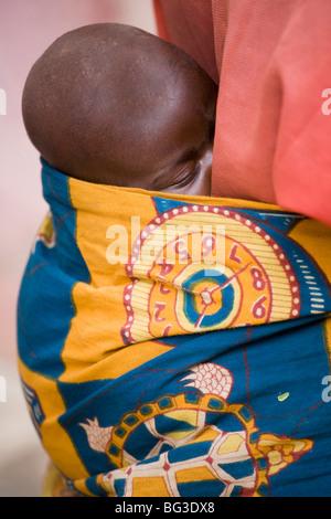 Baby being carried on mother's back, Village of Masango, Cibitoke Province, Burundi, Africa - Stock Photo