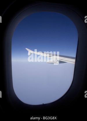 Air travel. View from the cabin window of an Airbus A319 passenger jet in flight, showing the aircraft's wing - Stock Photo