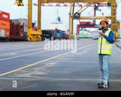 A man on the job, talking into a radio. - Stock Photo