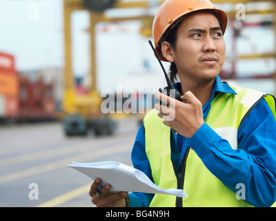 A man on the job, talking into a radio. - Stock Photo
